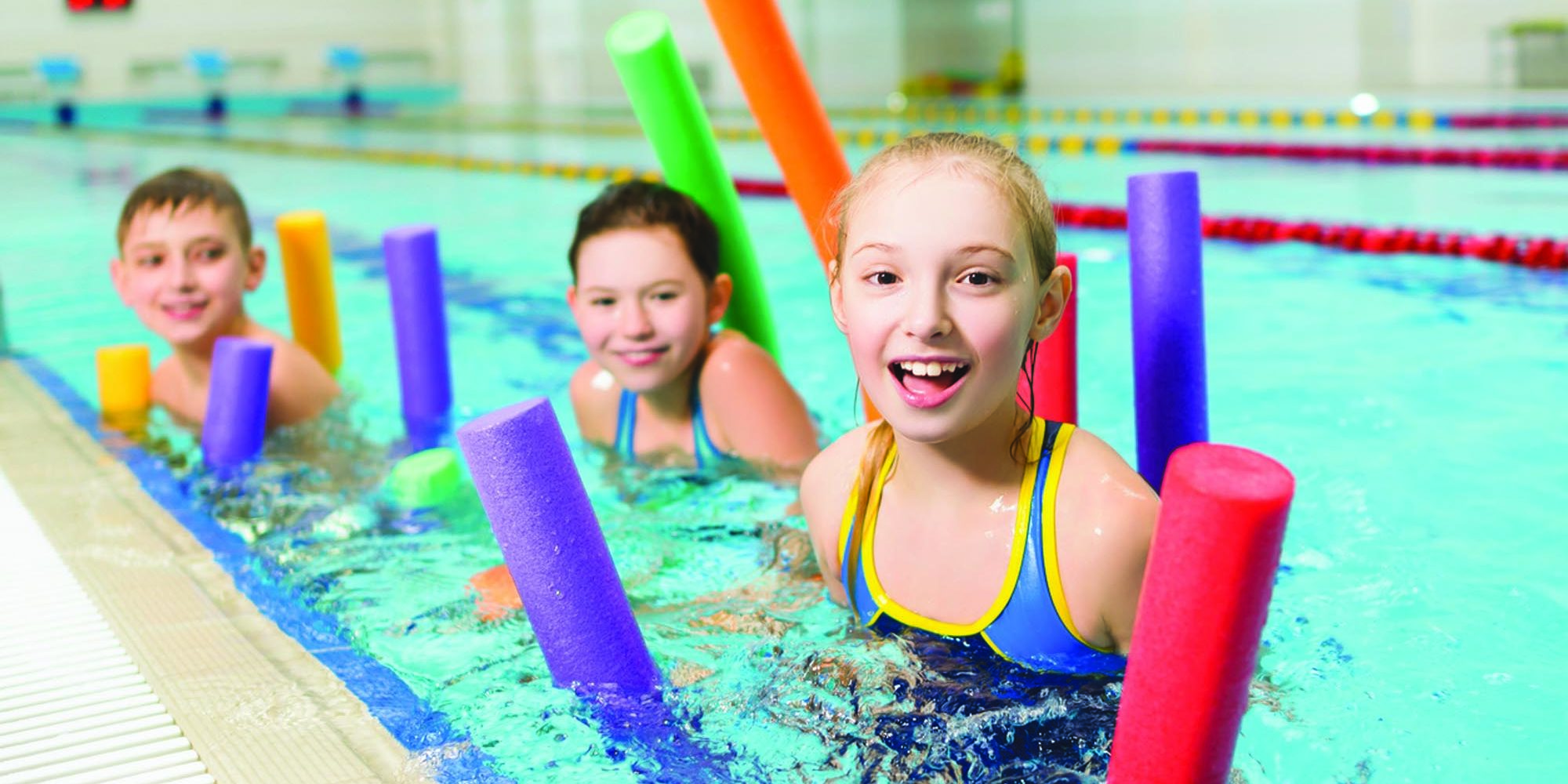 Happy and smiling group of children learning to swim with pool noodle.