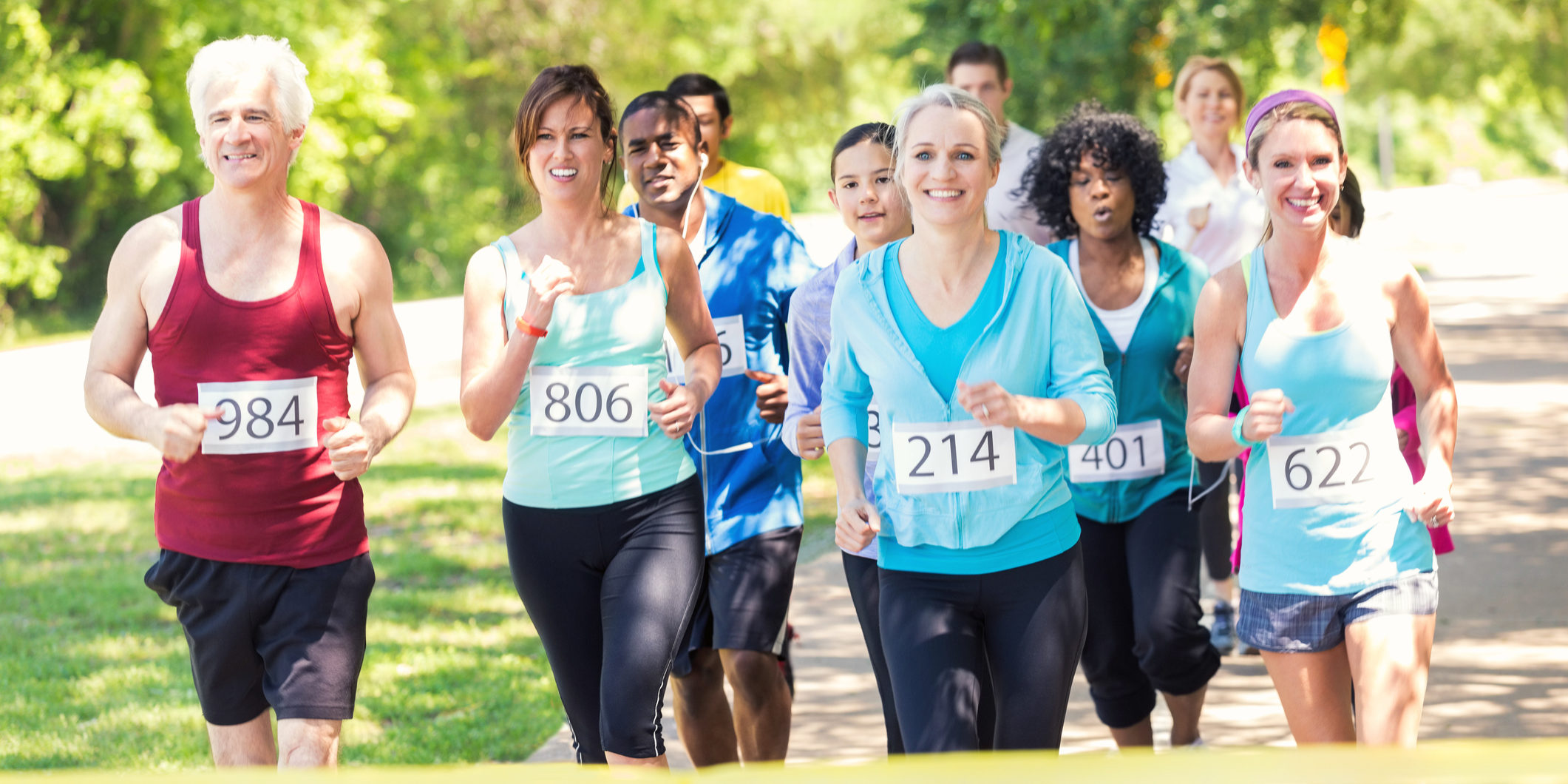 Diverse adults are smiling as they approach finish line during marathon or 5k race for charity. Senior adults, mature adults, mid and young adults are all participating in race at park on sunny day. They are wearing athletic clothing and race contestant numbers on their shirts.