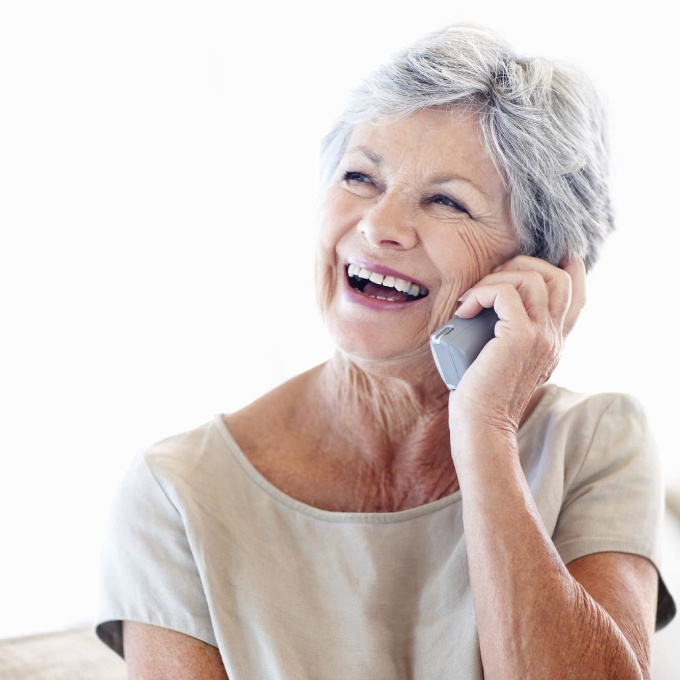 Cheerful senior woman using cordless phone at home