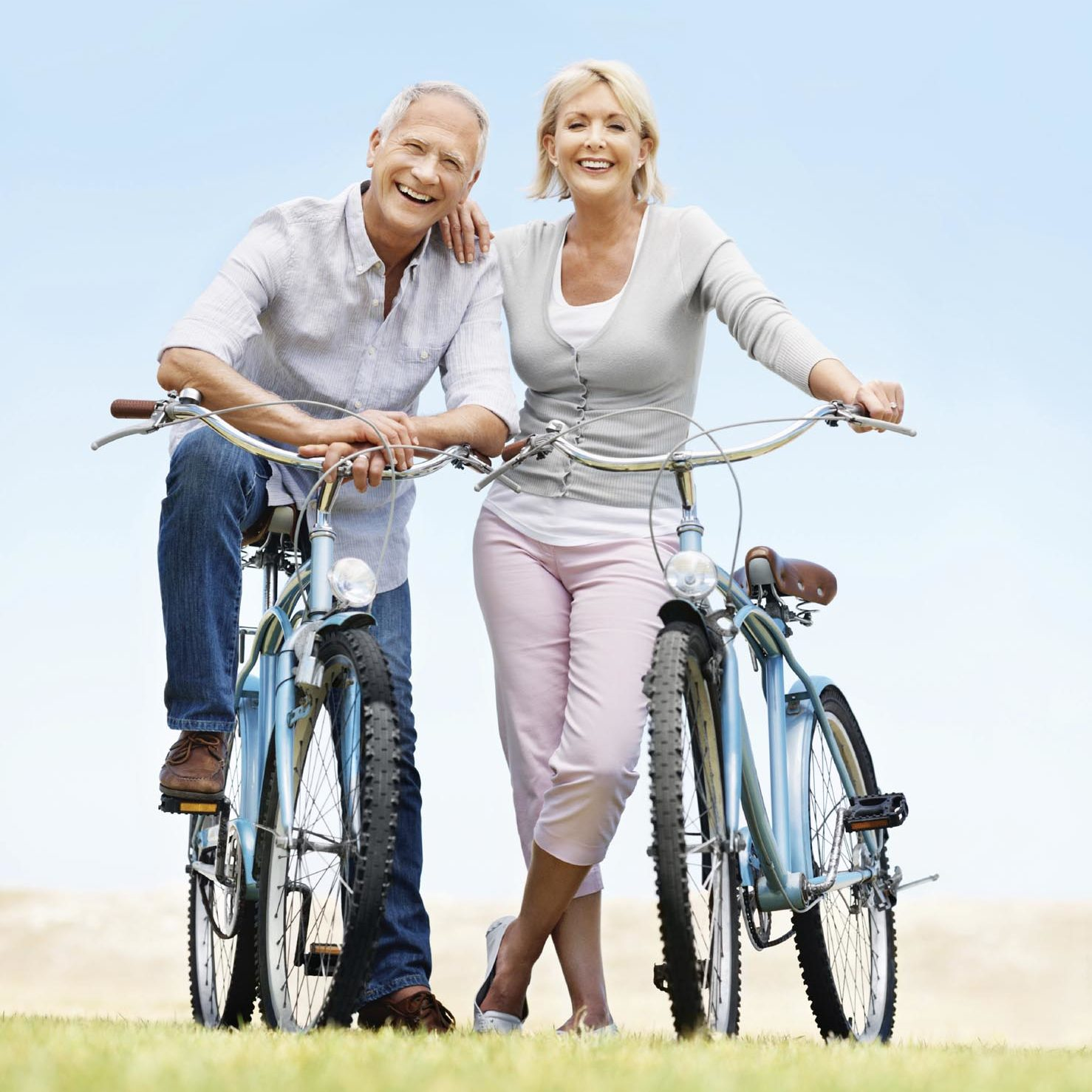 Full-length portrait of a mature couple with their bikes