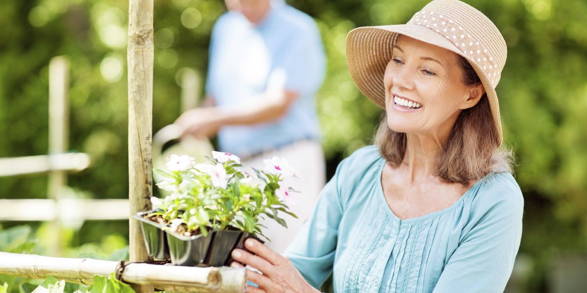 Happy senior woman looking at flower plants while man watering in background at garden. Horizontal shot.
