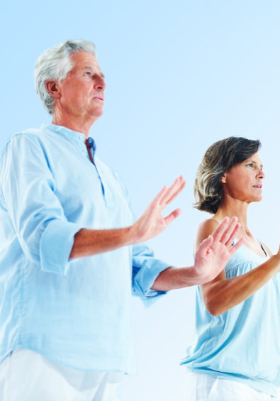 Portrait of an old couple practicing yoga with the blue sky as the background