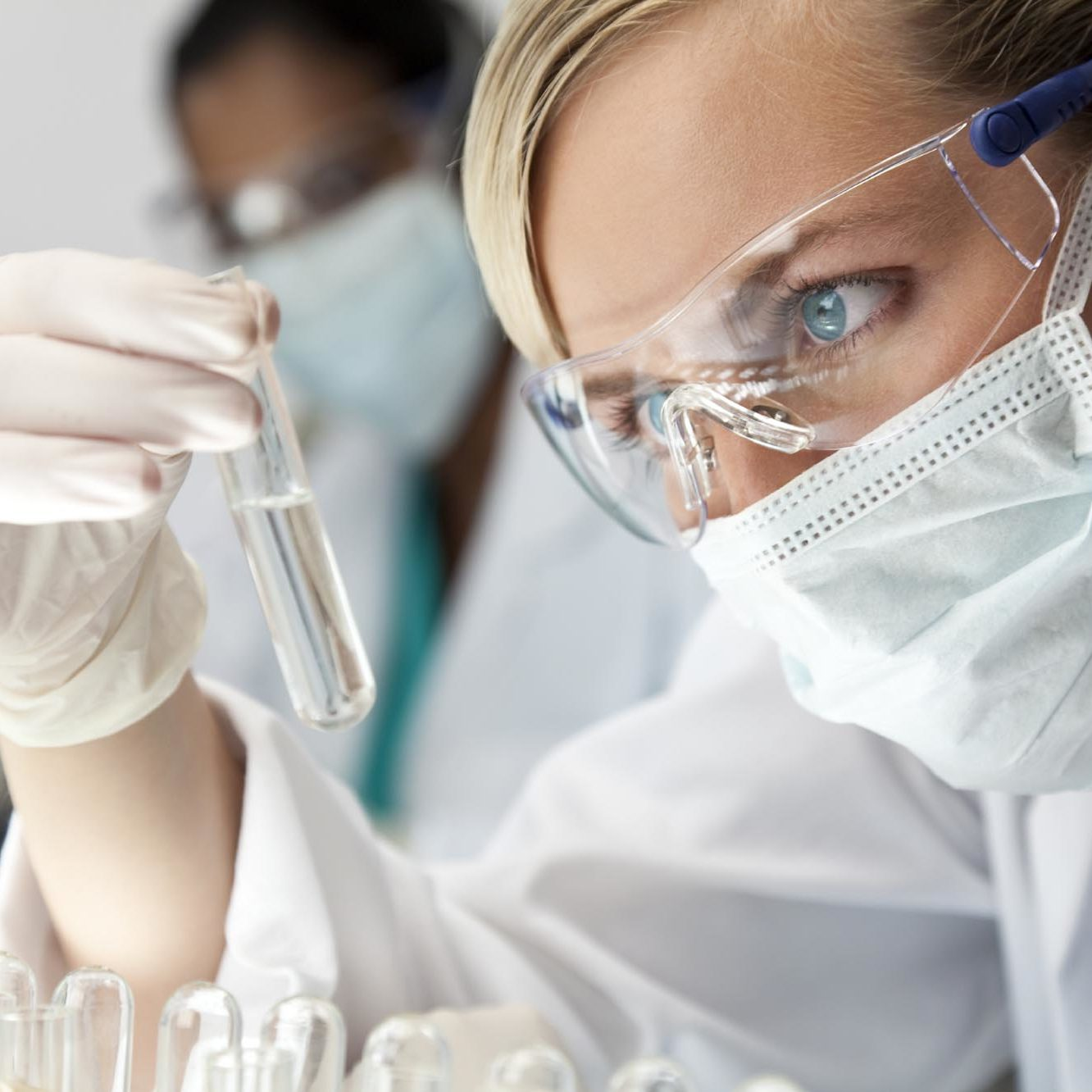 A blond medical or scientific researcher or doctor using looking at a clear solution in a laboratory with her Asian female colleague out of focus behind her.
